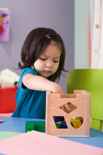 Girl playing with a wooden toy